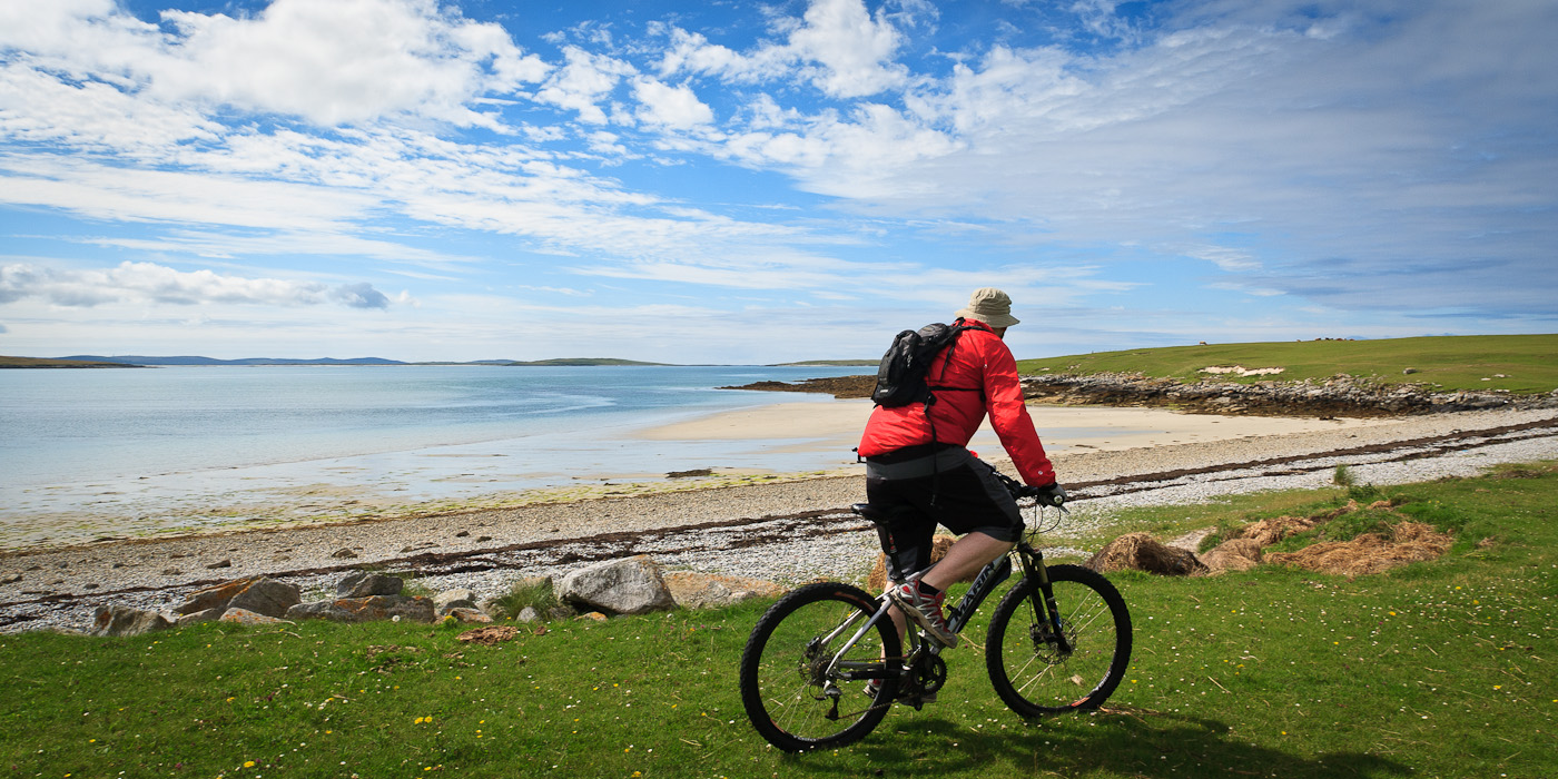 a men with red jacket cycling - things to do in Scotland